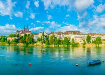 Riverside Of Rhine In Basel Dominated By Majestic Building Of Munster Church Switzerland